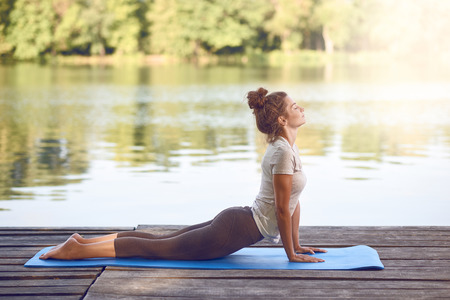 Attractive young woman working out on mat on a wooden deck above a lake or river doing a yoga pose with her eyes closed and a serene expression