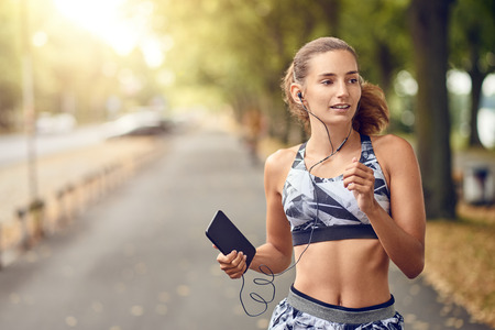 Fit healthy athletic woman jogging on a river bank smiling happily with her long hair flying out behind her as she approaches the camera