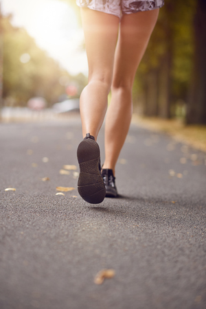 Young woman walking or jogging down an autumn street backlit by the glow of the evening sun in a low angle view of her shapely legs in shorts and sandals from the rear in mid stride