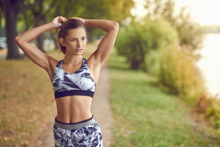 Slender fit shapely woman in sportswear walking along a shady tree lined path looking aside with her hands to her pony tail Stok Fotoğraf