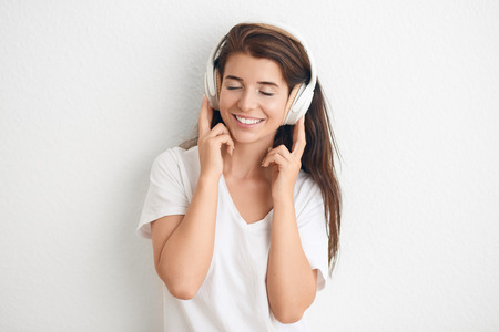 Attractive young woman closing her eyes as she listens to music on stereo headphones looking with a vivacious smile against a white wall with copy space