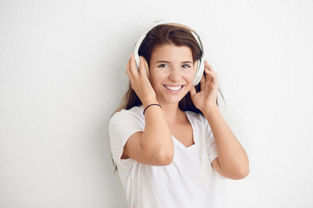 Attractive young woman laughing as she listens to music on stereo headphones looking at the camera with a vivacious smile against a white wall with copy space Stock Photo