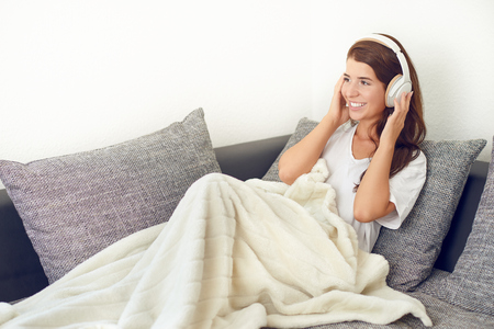 Smiling happy attractive vivacious young woman relaxing on a grey sofa with a rug over her legs listening to music on stereo headphones