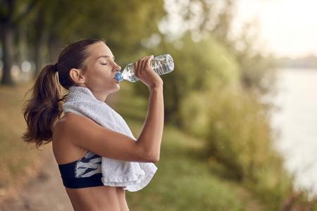 彼女は彼女の首の周りにタオルで木の並んだ歩道で彼女のジョギングワークアウト中に一時停止するようにペットボトルから水を飲むスポーティな女性をフィット