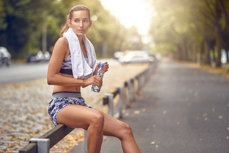 Happy fit woman taking a break from jogging sitting resting on a roadside railing as she drinks water from a bottle and smiles at the camera
