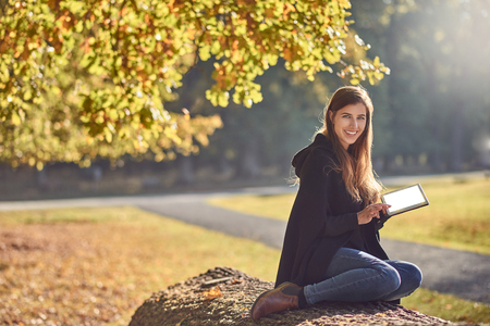 Pretty young woman relaxing in an autumn park reading on her tablet pc and smiling happily at the camera