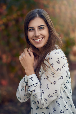 Attractive young woman in a colorful fall or autumn street standing sideways to the camera with her hand to her cheek smiling at the camera