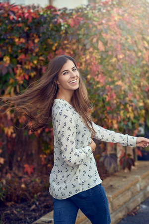 Carefree happy young woman tossing her hair as she looks back at the camera with a vivacious smile in front of colorful fall foliage