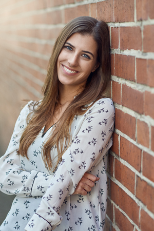 Attractive young woman with a lovely natural smile leaning against an exterior brick wall turning to look at the camera with flare to the side