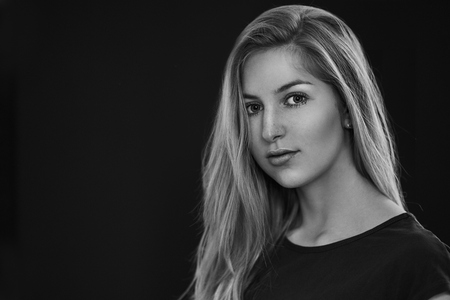Black and white portrait of beautiful young woman with straight blonde hair and pretty face. Half-turn bust portrait with on black background with copy space Stock fotó