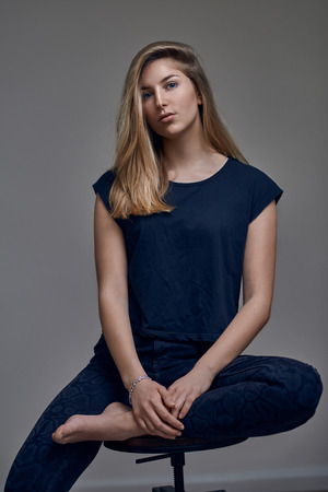 Beautiful young woman in blue t-shirt, with straight blond hair siting with one leg on chair and looking at camera. Front low angle portrait against grey background