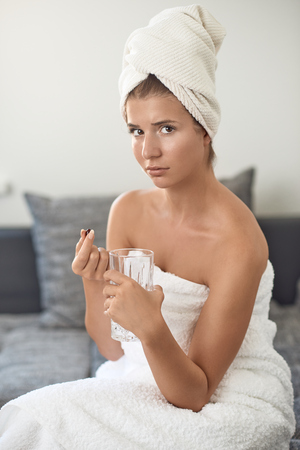 Attractive young woman with her hair and body wrapped in white towels after bathing or spa treatment taking a tablet or dietary supplement holding a glass of water looking thoughtfully at the camera