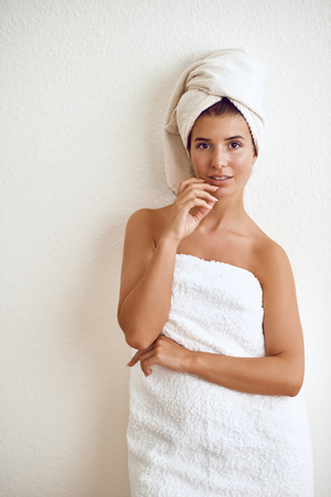 Smiling happy healthy attractive young woman wrapped in a clean fluffy white towel standing against a white wall conceptual of personal hygiene and spa treatments