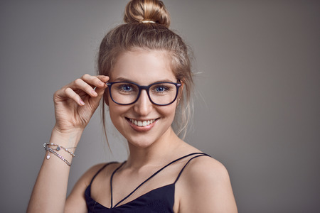 Attractive stylish blond woman with her hair in a bun wearing glasses smiling at the camera