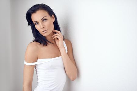 Portrait de beauté d'une femme d'âge moyen élancée en haut d'été blanc posant avec le bras levé vers ses longs cheveux bruns dans un geste sensuel contre un mur blanc avec espace de copie