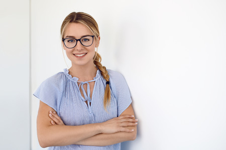 Friendly young blond woman wearing glasses with her long hair in a plait over one shoulder and folded arms smiling at the camera leaning on a white interior wall