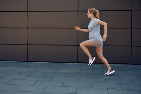 Pregnant young woman keeping fit sprinting along a paved sidewalk in front of an urban wall in a healthy lifestyle concept Stok Fotoğraf