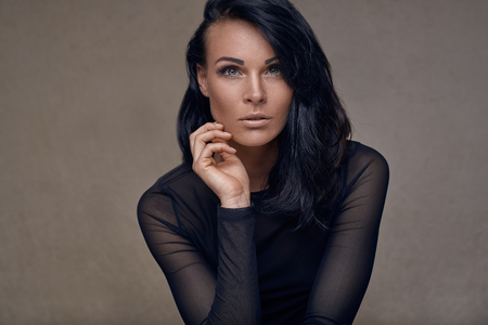 Beauty portrait of an attractive middle-aged woman in black top with long dark hair looking thoughtfully at the camera with hand raised to her chin over a grey studio background Фото со стока