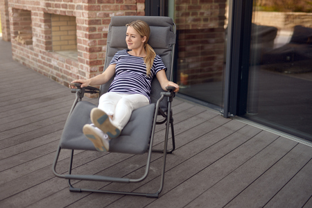 Happy smiling attractive young pregnant young woman relaxing outdoors on a recliner chair on a wooden deck cradling her baby bump in her hands Stock Photo