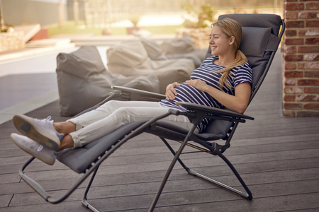 Happy smiling attractive young pregnant young woman relaxing outdoors on a recliner chair on a wooden deck cradling her baby bump in her hands Stockfoto
