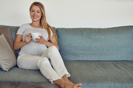 Pretty barefoot young pregnant woman relaxing on a couch drinking a cup of hot tea and smiling happily at the camera