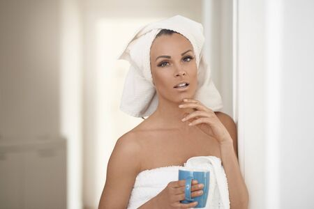 Pretty middle-aged woman wrapped in fresh clean white towels around her head and body leaning against an interior wall with a mug of beverage in a concept of healthy spa treatments and personal hygiene