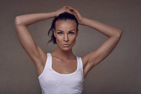 Sensual beautiful slim middle-aged woman in summer top posing with one hand to her chest and the other raised to her head as she looks at the camera with a serious expression over a brown studio background