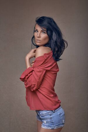 Schöne Frau in knappen Denim-Shorts mit ihrem Hemd, das provokativ von ihrer Schulter gerutscht ist und die Kamera mit geöffneten Lippen über einem braunen Studiohintergrund anschaut Standard-Bild