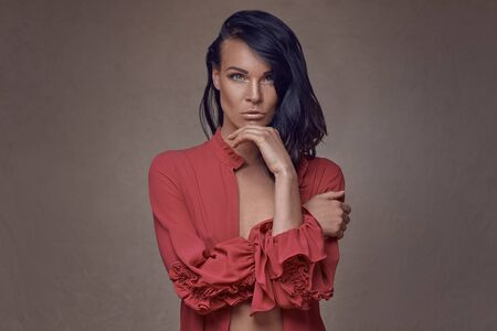 Sexy woman with unbuttoned red shirt covering her breasts and giving the camera a sultry look