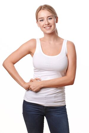Happy relaxed smiling young woman in jeans and t-shirt standing isolated on white Фото со стока