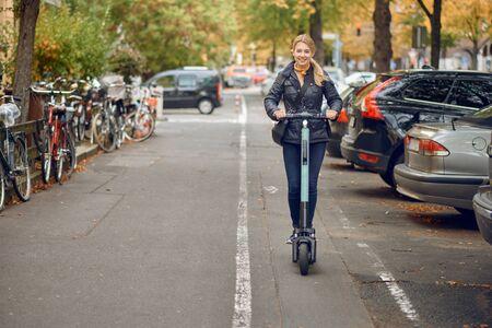 Joven mujer rubia feliz montando un scooter eléctrico en la ciudad, sonriendo a la cámara, en otoño Foto de archivo