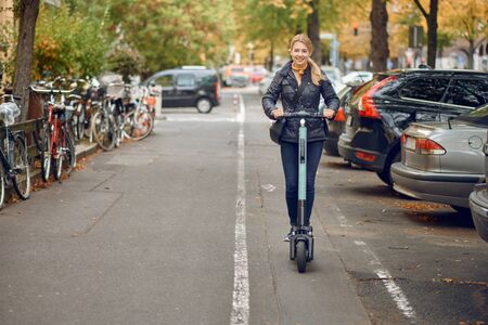 Young happy blond woman riding an electric scooter in the city, smiling at the camera, in autumn Stock Photo