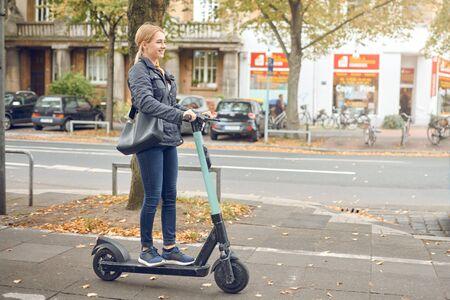Joven mujer rubia feliz montando un scooter eléctrico en la ciudad en otoño, vista lateral
