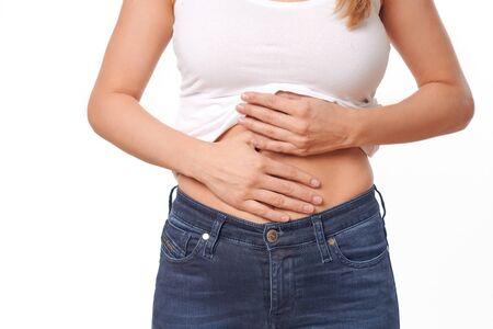 Frau mit ihren monatlichen Menstruationsschmerzen, die ihren Bauch mit den Händen umklammert, während sie durch die anhaltenden Krämpfe gestresst wird, Torsoansicht ihrer Hände und Bauch isoliert auf Weiß