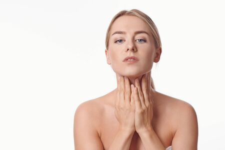 Beautiful young woman with bare shoulders massaging her throat with her hands in the morning to tone the skin and muscles and increase circulation or while applying a skin cream in a health and beauty concept