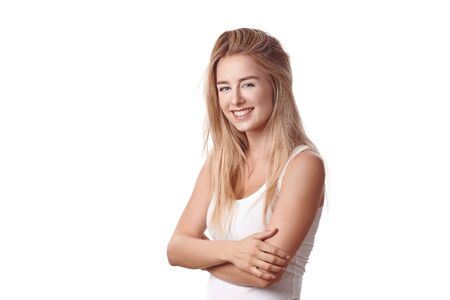 Beautiful blond young woman standing in white shirt with arms folded against white background, smiling and looking at camera. Half-turn half-length portrait Banco de Imagens
