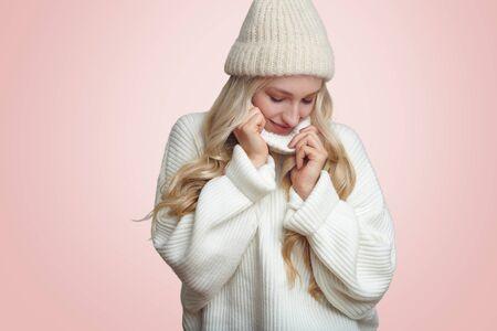 Giovane donna bionda in caldo maglione lavorato a maglia bianco e cappello invernale, in piedi su sfondo rosa chiaro e guardando in basso, godendosi la morbidezza dei vestiti Archivio Fotografico