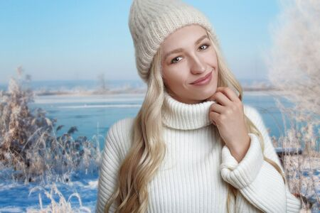 Young blond woman enjoying her white knitted sweater, standing against winter landscape background, with her hands to her sweater