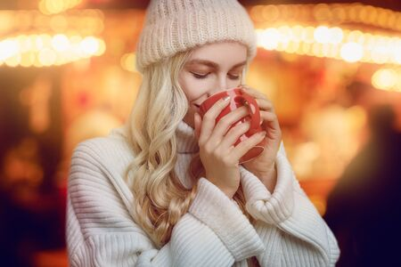 Young woman enjoying a mug of hot coffee in winter cupping it in her hands as she drinks with a blissful smile against a glowing warm orange background Standard-Bild