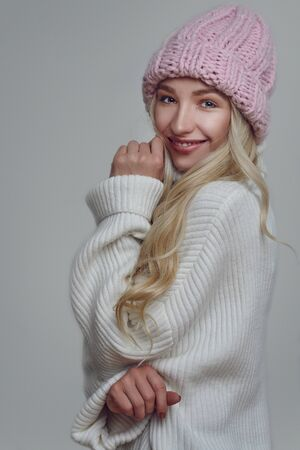 Happy young woman with long blond hair in pink knitted winter hat looking at the camera with a grey background Stockfoto