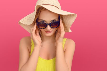 Attractive chic young woman in summer outfit with a large floppy sunhat peering over the top of her sunglasses at the camera with a friendly smile over a pink studio background