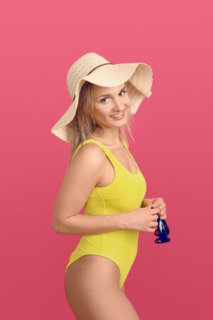 Slender attractive young blond woman in a colorful yellow swimsuit and wearing a wide-brimmed floppy straw sunhat looking to the side with a happy smile while holding her sunglasses on pink background Фото со стока