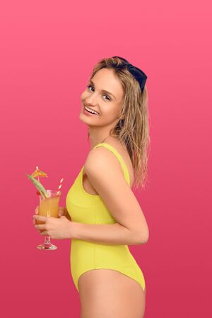 Attractive trendy blond woman with exotic tropical cocktail in a glass lifting her sunglasses to the top of her head as she smiles at the camera conceptual of summer vacation