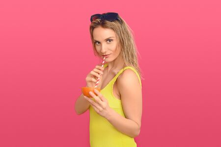 Young woman in yellow swimsuit drinking through a straw from a halved fresh orange conceptual of tropical cocktails on summer vacation or a healthy diet rich in vitamin C