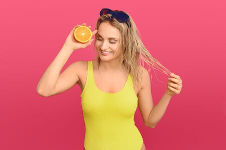 Happy healthy young woman holding a halved fresh juicy orange to her eye with a beaming friendly smile over a pink studio background Фото со стока