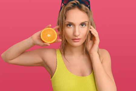 Pretty young blond woman with sunglasses on top of her head holding a fresh halved orange to her cheek as she looks thoughtfully at the camera over a pink background in close up Фото со стока