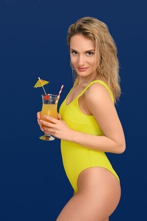 Attractive trendy blond woman with exotic tropical cocktail in a glass  as she smiles at the camera conceptual of summer vacation