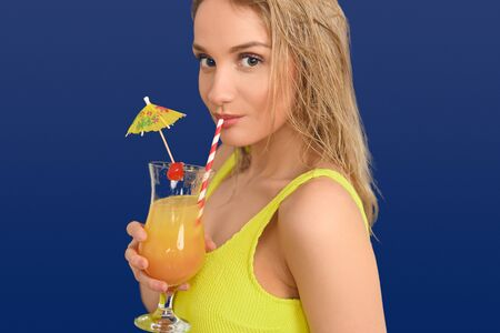 Young attractive blond woman in yellow sleeveless summer top sipping an exotic fruit cocktail on summer vacation over a blue background in close up as she glances sideways at the camera Фото со стока
