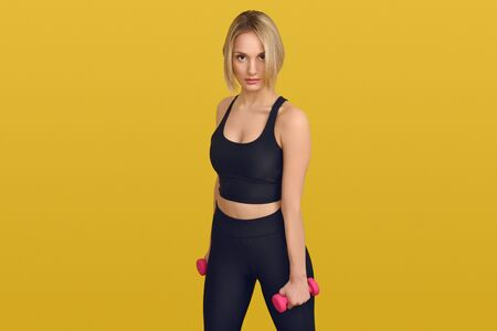 Pretty blond woman in black training top with small pink dumbbells in her hands, looking at camera. Close-up front portrait against plain yellow background
