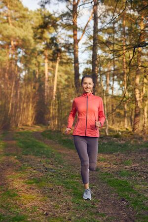 Healthy fit attractive young woman jogging in woodland along a forest track approaching the camera with a happy smile in an active lifestyle, health and fitness concept